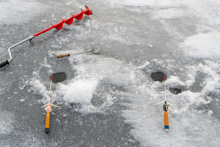 boer: Fishing tackle for ice fishing such as the boer and fishing rod near the ice-hole on ice