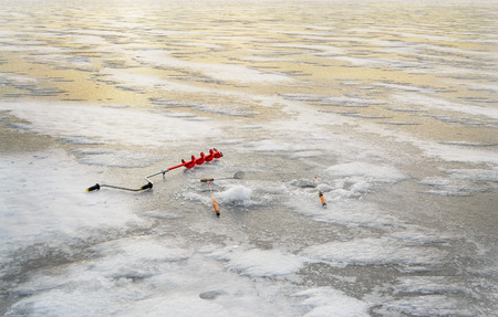 boer: Fishing tackle for ice fishing such as a boer and fishing rod near the ice-hole on ice