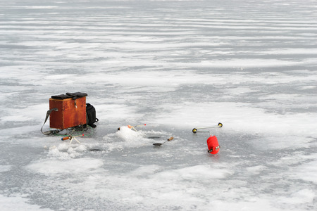 boer: Fishing tackle for ice fishing such as a boer, a fishing rod and a box near the ice-hole on ice