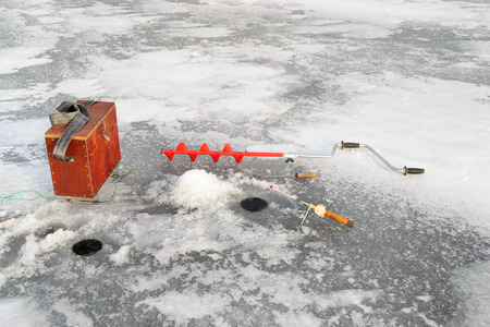 boer: Fishing tackle for ice fishing such as a boer, fishing rod and box near the ice-hole on ice Stock Photo