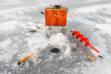 boer: Fishing tackle for ice fishing such as a boer, a fishing rod and box near the ice-hole on ice Stock Photo