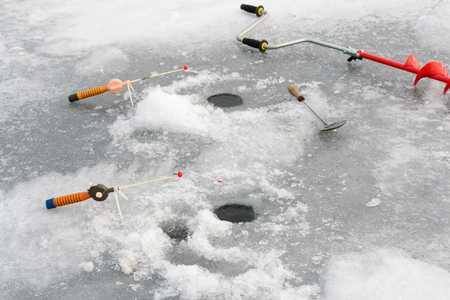 boer: Fishing tackle for ice fishing such as a boer and a fishing rod near the ice-hole on ice