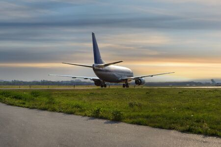 Airplane on the runway after landing at airport on cloudy sky background at sunset  Stock Photo