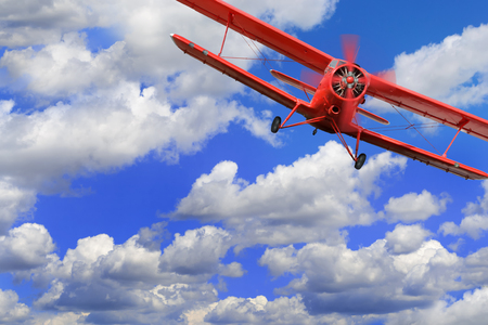 Red airplane biplane with piston engine flies and makes turn in cloudy sky Reklamní fotografie