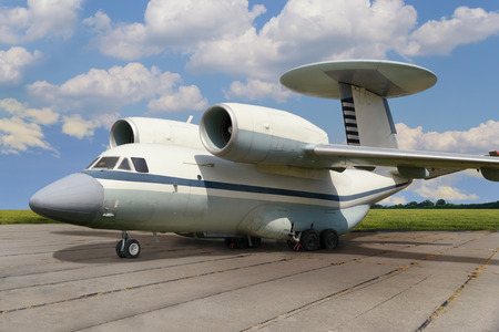Side view of jet airplane with turbojet engines and radar antenna on tail at parking against of blue cloudy sky