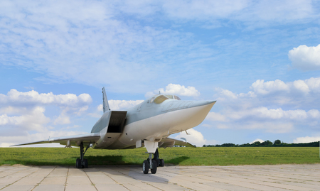 Military jet supersonic aircraft in the parking of the airfield against of the blue cloudy sky