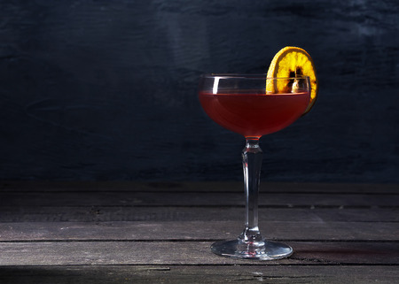 Alcohol cocktail drink with slice of orange on the wooden rustic background