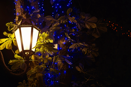 Vintage street lamp, bokeh lights and leaves of trees, night background Stock Photo