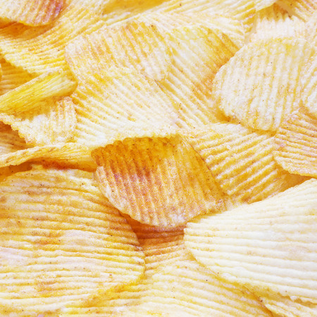 waved: golden closeup wavy potato chips food background, selective focus