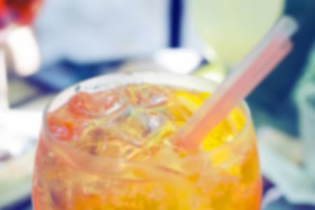 spritz: One glass of spritz cocktail with orange slices; blurred background