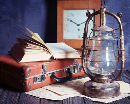 vintage travel still life with kerosene lamp, book and suitcase