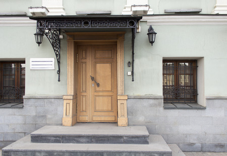 view of a wooden doorway: classical facade with steps and forged canopy Stock Photo