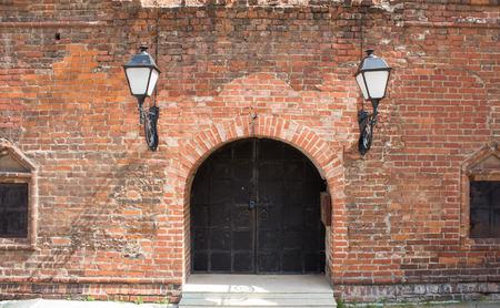 puertas de hierro: antigua fachada de ladrillo con puertas de hierro y persianas