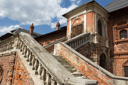 stucco facade: old facade with a picturesque staircase made of brick and stucco Stock Photo