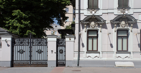 wicket door: classical facade, two windows and an iron gate with wicket door Stock Photo
