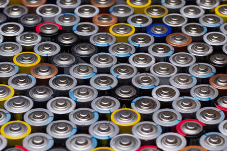 Several used stacked AAA batteries of different colors and manufacturers