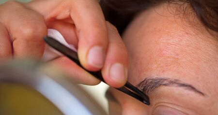 plucking: Plucking eyebrows Stock Photo
