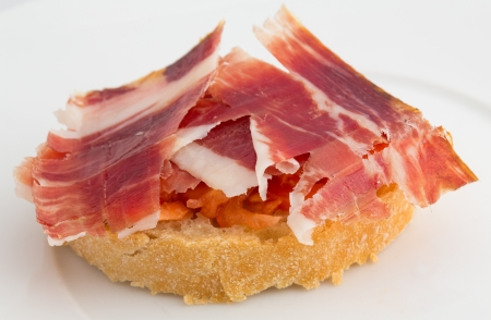 Spanish tapa, ham and tomato Imagens