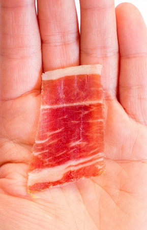 Serrano ham slice and hand photo