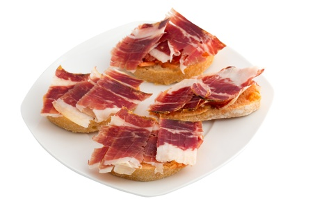 Spanish tapas, ham and tomato Imagens