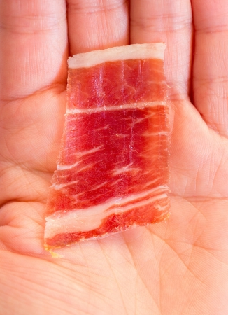 Serrano ham slice and hand Stock Photo - 16969431