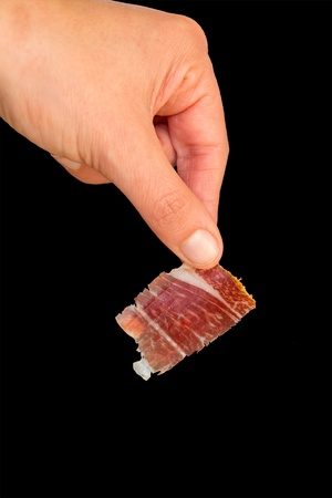 Picking serrano ham with left hand photo