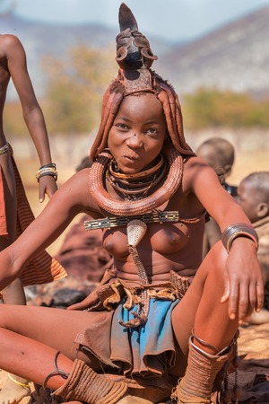 EPUPA, NAMIBIA - AUGUST 4: An unidentified Himba woman smiles while tourists visit the the himba settlement on August 4, 2013 in Namibia