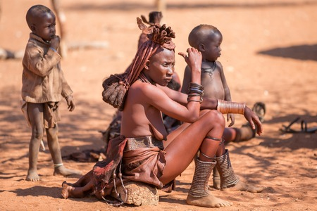 EPUPA, NAMIBIA - AUGUST 4: An unidentified Himba woman stands behind several children while tourists visit the the settlement on August 4, 2013 in Namibia