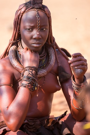 EPUPA, NAMIBIA - AUGUST 4: An unidentified Himba woman stands serious while tourists visit the the settlement on August 4, 2013 in Namibia Editorial