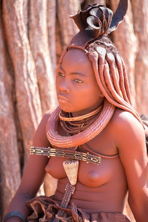 EPUPA, NAMIBIA - AUGUST 4: An unidentified Himba woman stands while tourists visit the the himba settlement on August 4, 2013 in Namibia