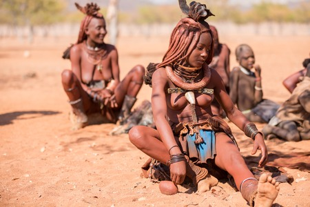 EPUPA, NAMIBIA - AUGUST 4: An unidentified Himba woman stands behind other himba women while tourists visit the the settlement on August 4, 2013 in Namibia