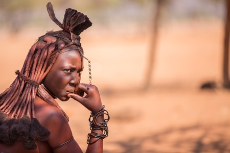 EPUPA, NAMIBIA - AUGUST 4: An unidentified Himba woman thoughful while tourists visit the the himba settlement on August 4, 2013 in Namibia