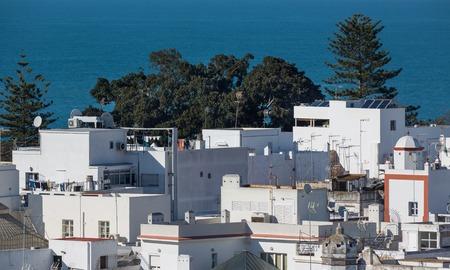 privileged: View of modern white buildings against ocean
