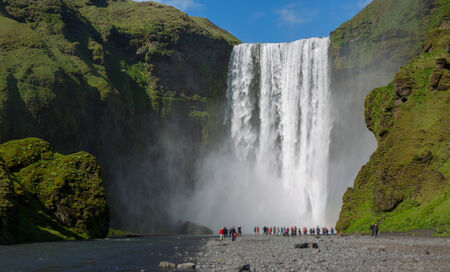 Blurred tourists under Skogafoss waterfall on the South of Iceland near the town Skogar photo
