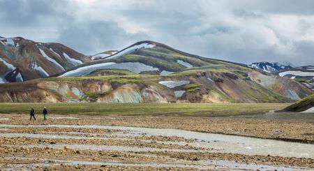 unbelievable: Blurred Tourists walking across Landmannalaugar unbelievable landscape, Iceland Stock Photo