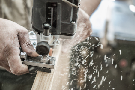 Blurred motion of carpenter working, preparing door for hinges Stock Photo