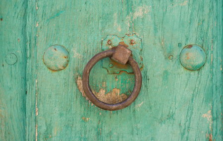 view of a wooden doorway: Front view of old doorknocker and green painted wooden door
