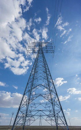 vertical composition: Centered Electric tower over blue sky and clouds, vertical composition