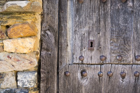 view of a wooden doorway: Front view of old lock and wooden door with iron nails