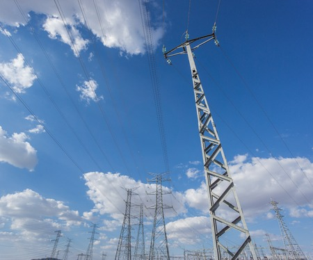 Wide view of electric tower group over blue sky and clouds photo