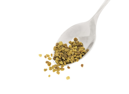 Side view of silver spoon with bee pollen, white background photo