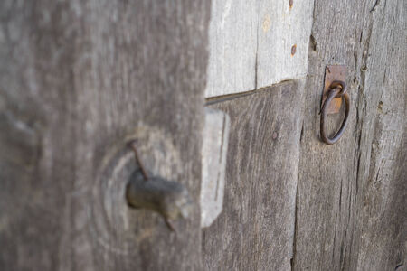 lock out: Old run-down wooden door and wooden lock out of focus