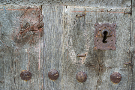 view of a wooden doorway: Old run-down wooden door and iron lock