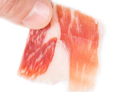 Top view of caucasian man hand taking Serrano ham slice on white photo