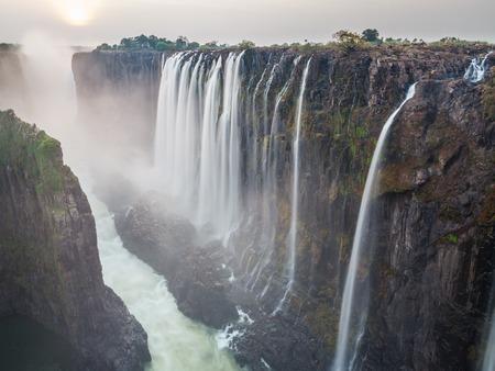 Victoria Falls sunset, Zambia side with zambezi river, red sun, long exposure