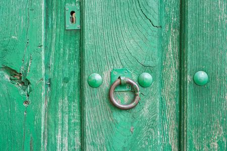 doorknocker: Old run-down green painted wooden door and iron nails