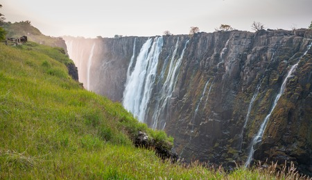 zambezi: Victoria Falls sunset with zambezi river and tourists, View from Zambia Stock Photo