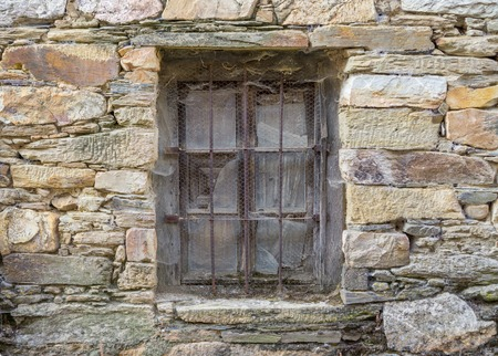 grille': Old window with grille and stone wall