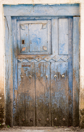 view of a wooden doorway: Entire old blue painted wooden door and lock Stock Photo