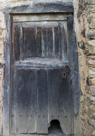 view of a wooden doorway: Entire old wooden door with cathole (cat flap)